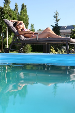 young woman sunbathing by the pool photo
