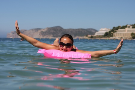 Happy woman relaxing on an mattress in sea photo