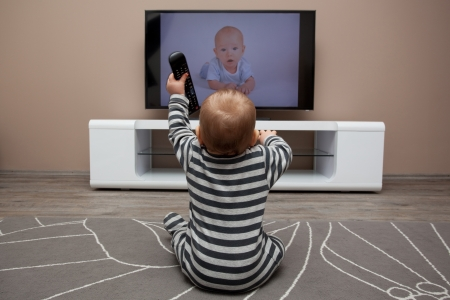 baby boy with remote controls watching television photo