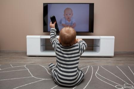 ver tv: Bebé con los mandos a distancia viendo la televisión Foto de archivo