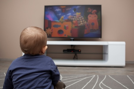 baby boy watching TV at home photo