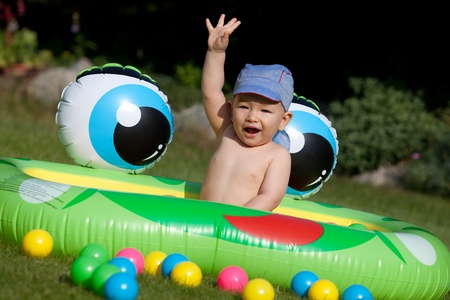 Laughing baby boy sitting in a kids rubber pool  Hand up  photo