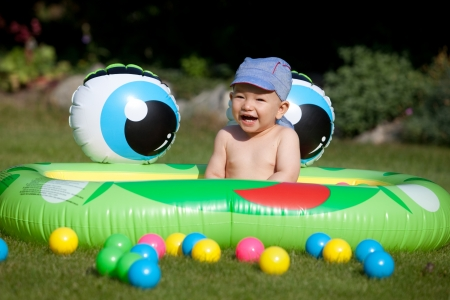 Laughing baby boy sitting in a kids rubber pool photo