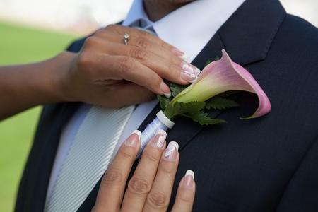 fidelidad: La organizaci?n de novia flor en el ojal de flores en traje de novia jacke Foto de archivo
