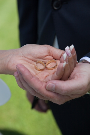 Wedding detail of the rings and hands holding photo