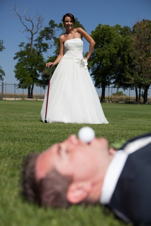 Bride and groom playing golf