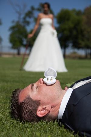 wed: Wedding rings and groom  Bride standing in background