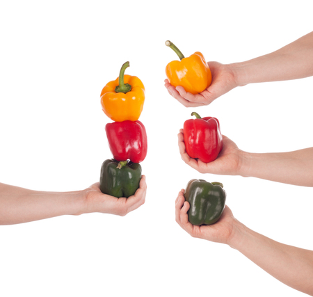 Orange, red and green pepper in hand, isolated on white background photo