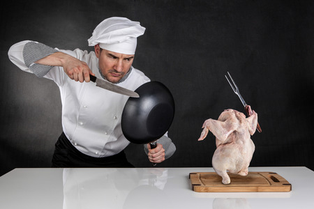 Chef fighting with knife and pan  Raw chicken attack Standard-Bild