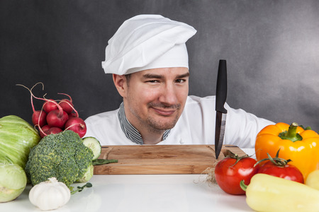 Young chef with knife and vegetable on black