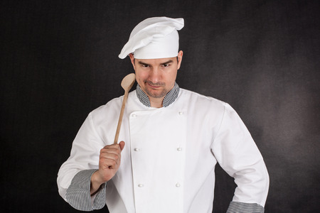 Chef holding wooden spoon on black background