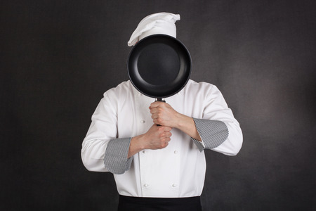 Chef behind pan black background Stock Photo