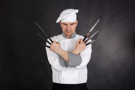 Chef with knifes arms crossed on black background