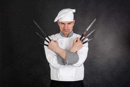 cuchillos: Cocinero con cuchillos los brazos cruzados sobre fondo negro