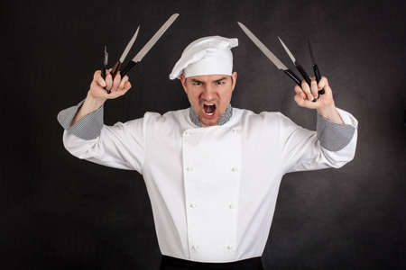 Angry chef with knifes on black background photo