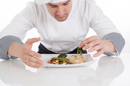 Chef decorating prepared food on white background