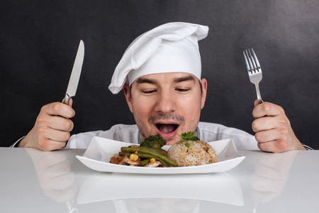 Chef eating his prepared food with cutlery  Black background