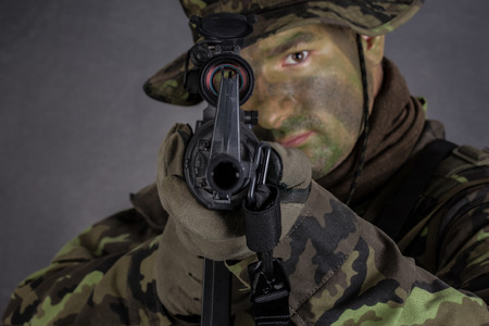 Soldier in camouflage and modern weapon M4 on black