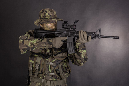 Soldier in camouflage and modern weapon M4 on black background photo