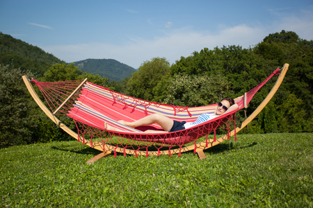 panoramatic: Young female relaxing in a hammock at hill top