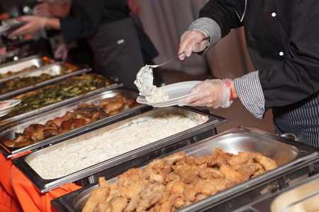 serving: Hands of cook serving food at a catered event Stock Photo