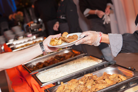 Hands of cook serving food at a catered event Stock Photo