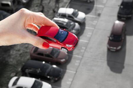 dream car: Sueño con tener un coche. Mano que sostiene un coche de juguete de color rojo sobre el aparcamiento.