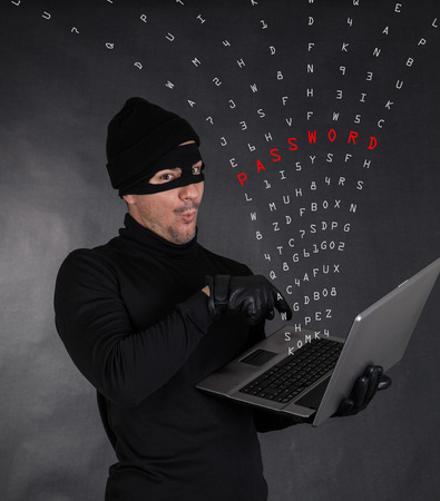 thievery: Hacker stealing data from a laptop on black background