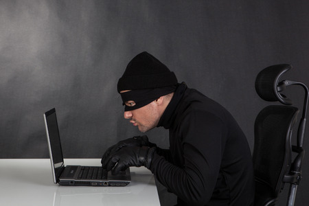 Hacker stealing data from a laptop on black background photo