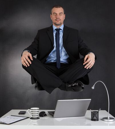 levitation: Businessman meditating in the office and in the air Stock Photo
