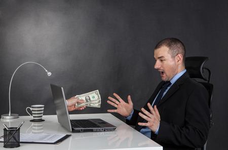 dolar: El hombre de negocios ganar dinero en la red. �l est� recibiendo dinero dolar a trav�s de Internet. Foto de archivo