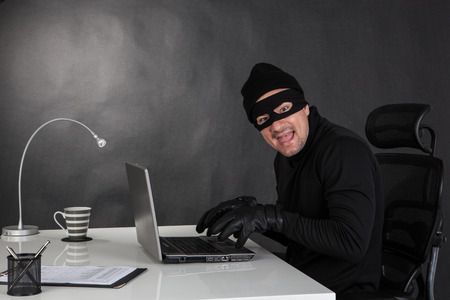 breaking the code: Hacker stealing data from a laptop and laughing
