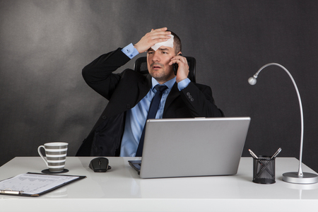 Bad news. Businessman holding forehead in office. Black background