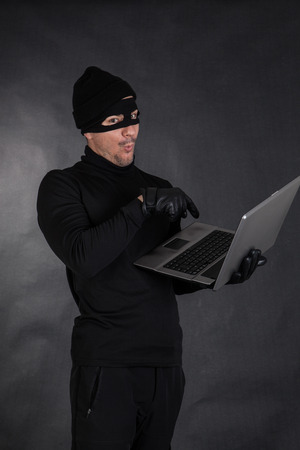 intruding: Hacker stealing data from a laptop on black background