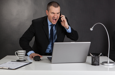 Angry businessman screaming on the phone. Stock Photo