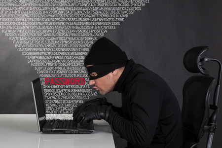 threats: Hacker stealing data from a laptop on black background