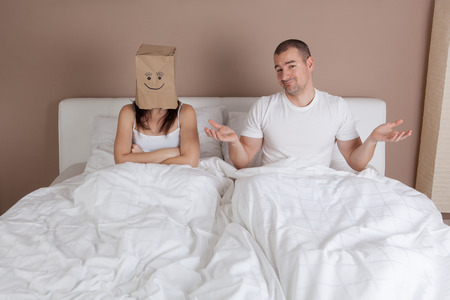 Funny situation in bed. Young couple lying in bed and woman with paper bag over head Stock Photo