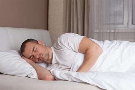 gente durmiendo: Hombre joven que duerme en una cama