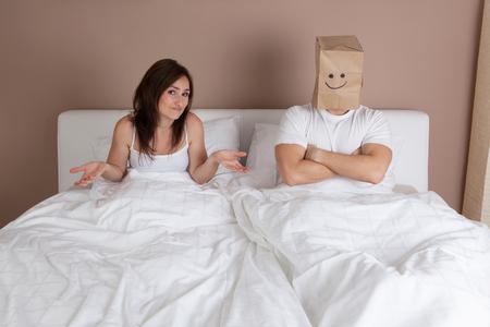 pareja en la cama: Situación divertida en la cama. Pareja joven tumbado en la cama y el hombre con la bolsa de papel de arriba