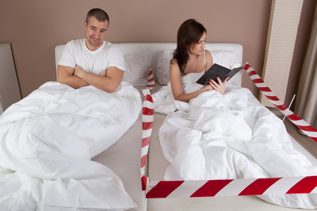 bed: Young couple having problem. Woman lying separately from husband on the bed and reading a book.
