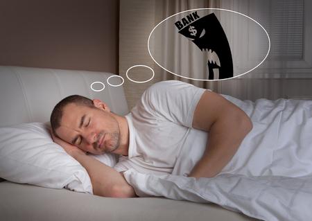 restless: Sleeping young man having a bad dream – bank and mortgage