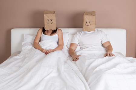 novios enojados: joven pareja en la cama con bolsas de papel sobre las cabezas Foto de archivo