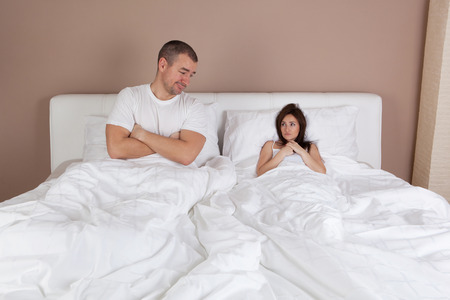 adult nude: Funny situation in bed. Young couple lying in bed and woman is very small Stock Photo