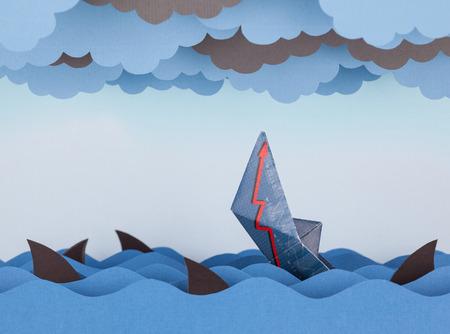 derrumbe: Barco de papel se hunde en el papel del mar. olas de papel, las nubes y los tiburones. Concepto de crisis y el colapso econ�mico.