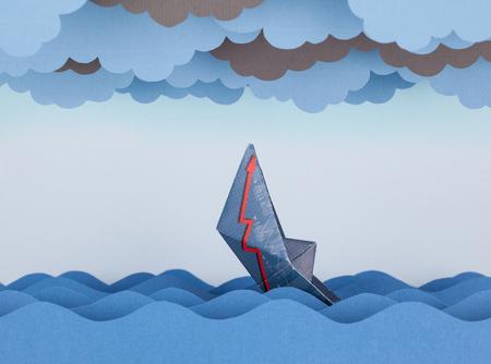 derrumbe: Barco de papel se hunde en el mar de papel. olas de papel y nubes. Concepto de crisis y el colapso económico. Foto de archivo