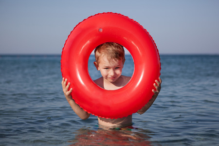 Little boy look out of inflatable ring in the sea Stock Photo
