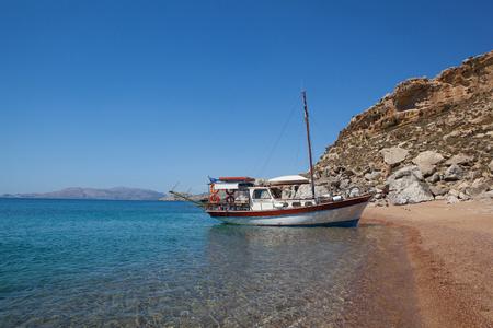 Red sand beach with ship, Rhodes island, Greece