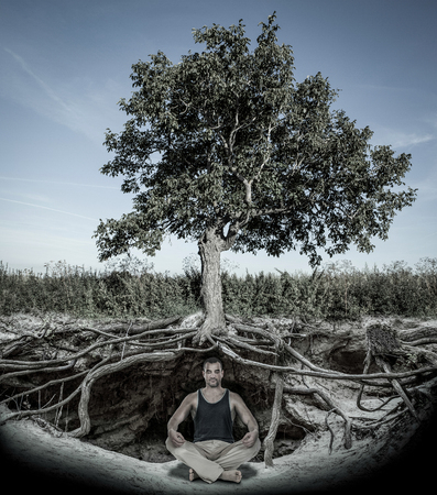 Young man meditating under tree with roots