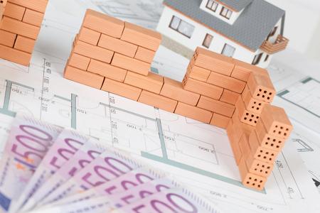 Closeup of model house construction with brick on blueprint Stok Fotoğraf