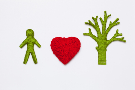 Yarn red heart, green tree and human figure isolated on white. Ecology concept Stock Photo